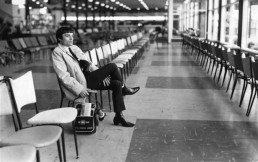 black and white picture of man seating and holding his bag